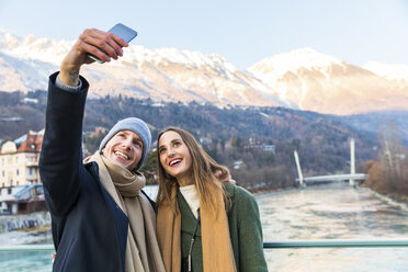Austria, Innsbruck, portrait of happy young couple taking selfie with smartphone in winter - WPEF00225