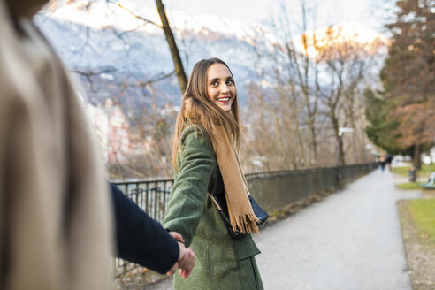 Austria, Innsbruck, portrait of happy young woman strolling hand in hand with her boyfriend at winter time - WPEF00231