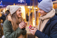 Happy young couple drinking mulled wine at Christmas market - WPEF00240