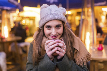 Portrait of content young woman drinking mulled wine at Christmas market - WPEF00243