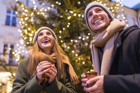 Laughing young couple drinking mulled wine at Christmas market - WPEF00246