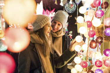 Young couple watching offerings at Christmas market - WPEF00249