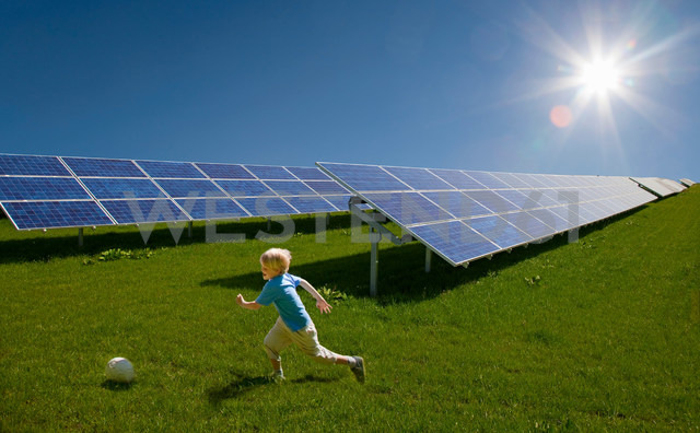 Boy playing in field by solar panels - CUF00754
