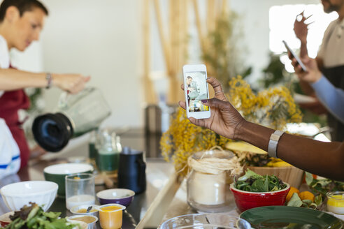 Close-up of woman taking smartphone picture of instructor working in a cooking workshop - EBSF02426