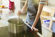 Woman stirring in cooking pot in kitchen - EBSF02441