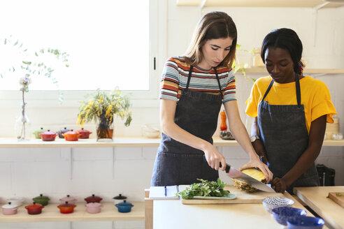Friends preparing pineapple in kitchen - EBSF02450
