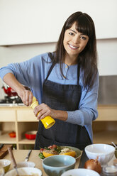 Portrait of smiling woman in kitchen - EBSF02453