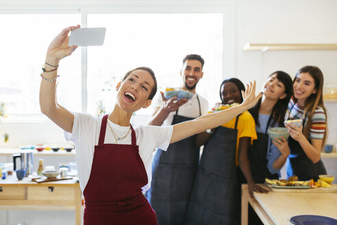 Playful instructor taking a selfie with friends in a cooking workshop - EBSF02465