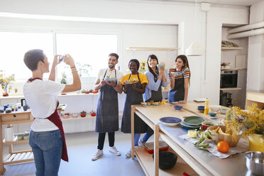 Instructor taking a picture of friends in a cooking workshop - EBSF02480