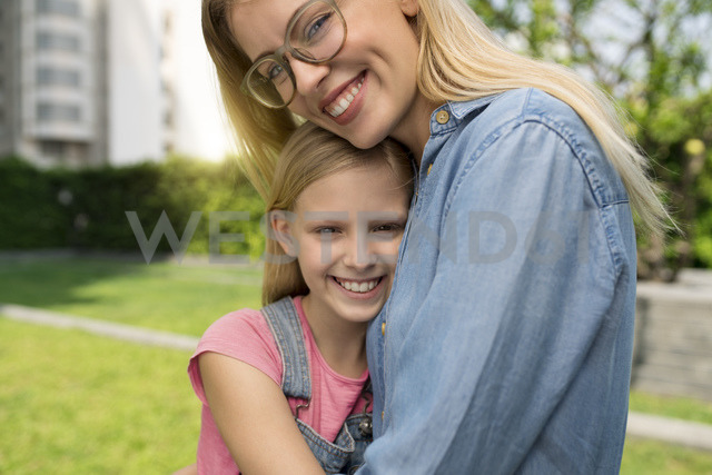 Happy mother and daughter hugging and smiling in urban city garden - SBOF01462