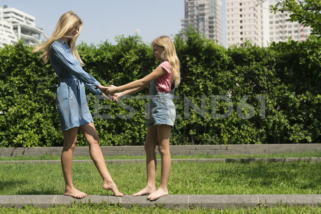 Happy mother and daughter holding hands in urban city garden - SBOF01465