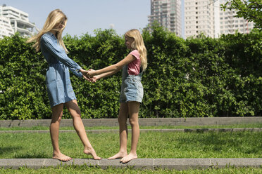 Happy mother and daughter holding hands in urban city garden - SBOF01465