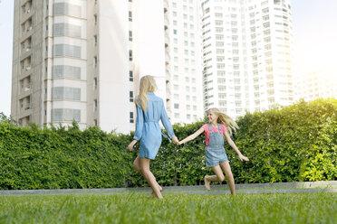 Happy mother and daughter having fun in urban city garden - SBOF01471