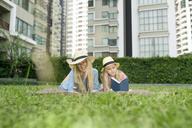 Happy mother and daughter with book and smartphone in urban city garden - SBOF01474