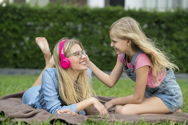 Happy mother and daughter listening to music together in garden - SBOF01477