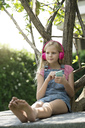 Cute blonde girl listening to music with pink headphones in garden - SBOF01480