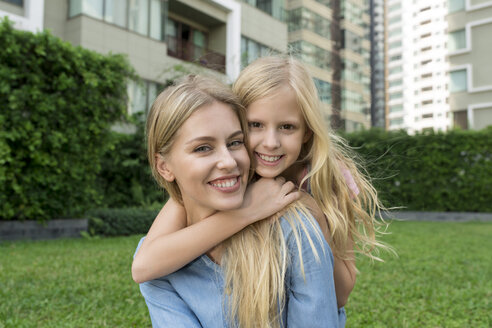 Happy mother and daughter hugging and smiling in urban city garden - SBOF01483