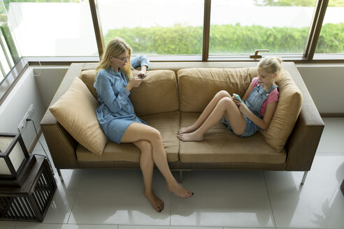 Mother and daughter sitting in modern living room on a couch using smartphones - SBOF01489