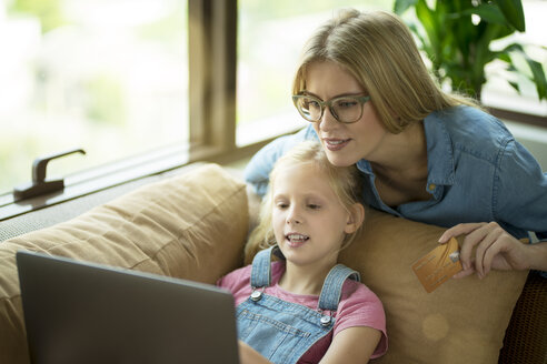 Mother and daughter in modern living room on a couch with laptop and credit card - SBOF01492