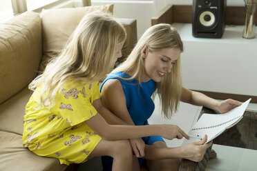 Happy mother and daughter sitting on a couch looking at a notepad together - SBOF01495