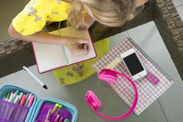 Girl doing her homework writing in booklet on table in living room - SBOF01498