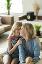 Happy mother and daughter cuddling and relaxing on a couch in a modern living room - SBOF01501