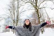 Woman in snowy woods embracing sky - CUF00853