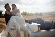 Newlywed groom carrying bride outdoors - CUF00910