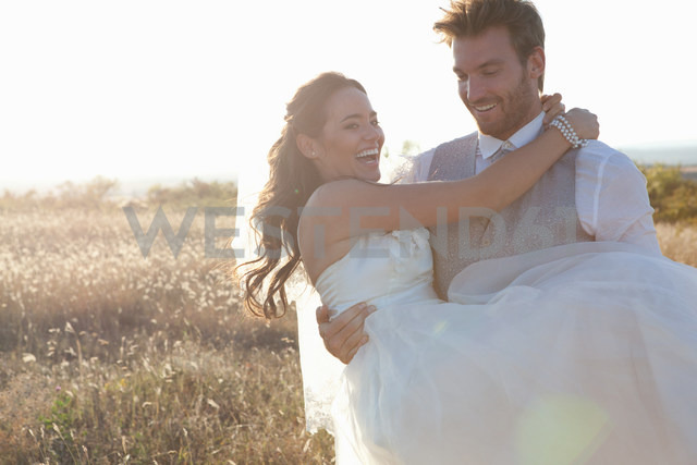 Newlywed groom carrying bride outdoors - CUF00916