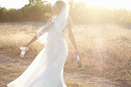 Newlywed bride carrying champagne - CUF00919