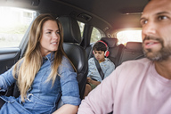 Family on a road trip with boy wearing headphones - DIGF04136