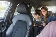 Family on a road trip with mother and son sharing tablet - DIGF04139
