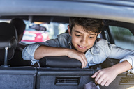 Smiling boy in car looking in boot - DIGF04142