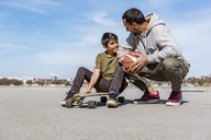 Father and son with longboard and basketball outdoors - DIGF04157