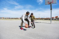 Father and son playing basketball on court outdoors - DIGF04163
