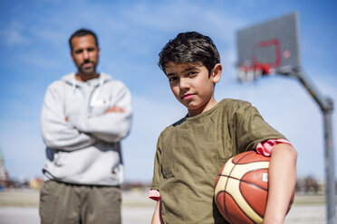 Portrait of boy posing with father on basketball court outdoors - DIGF04166
