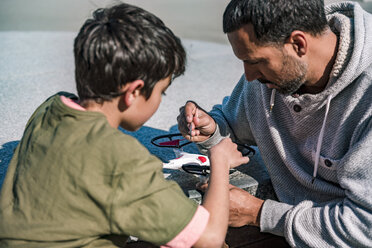 Father and son repairing drone - DIGF04175