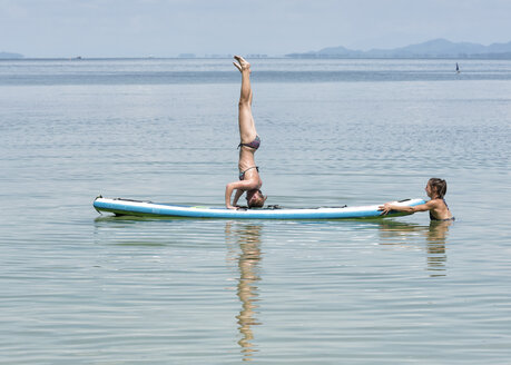 Thailand, Krabi, Lao Liang, woman doing a headstand on SUP Board in the ocean - ALRF01161