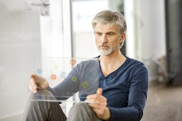 Mature businessman using transparent touchscreen computer - FMKF05062