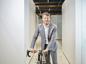 Portrait of smiling businessman with bicycle on office floor - CVF00346