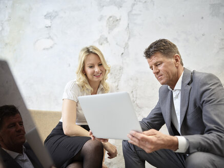 Businessman and businesswoman sharing tablet in modern office - CVF00349