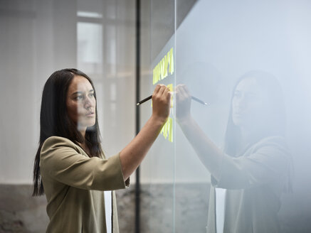 Businesswoman writing on sticky notes at glass pane in office - CVF00370