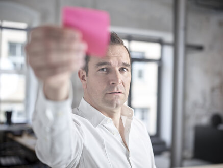 Businessman with sticky note in office - CVF00373