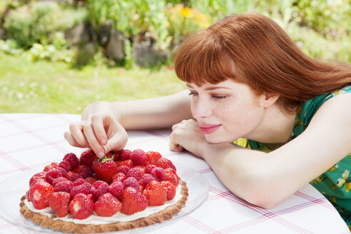 Young woman picking strawberry of tart. - CUF01088