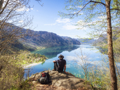 Italy, Lombardy, spring at Lake Idro, hiker sitting on observation point - LAF02018