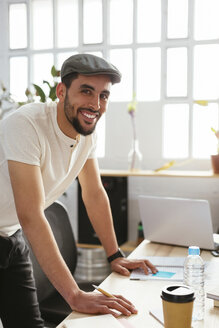 Portrait of smiling young man taking notes at desk in office - EBSF02500