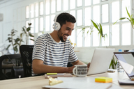 Laughing young man wearing headphones using laptop at desk in office - EBSF02509