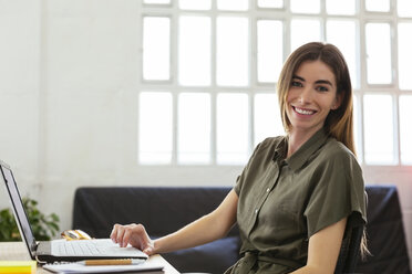 Portrait of smiling young woman with laptop at desk in office - EBSF02512