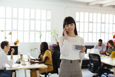 Portrait of smiling young woman on cell phone in office with colleagues in background - EBSF02527