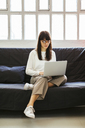 Young woman sitting on couch in office using laptop - EBSF02542